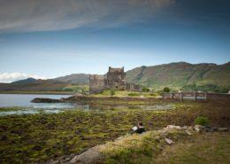 Mann mit Buch vor Eilean Donan Castle