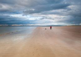 Spaziergängerin mit Hund am Strand von Dornoch Schottland