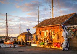 Mit Fischerei-Utensilien geschmücktes Bootshaus im Hafen von Gager Rügen