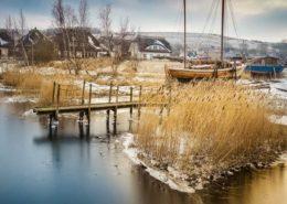 Bootssteg und Häuser in Gager Rügen im Winter