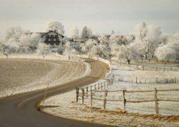 Raureif auf den Feldern und Bäumen in einem kleinen bayerischen Weiler