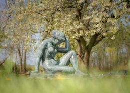 Frühling. Skulptur und blühende Kirschen im Park von Schloss Spyker Rügen